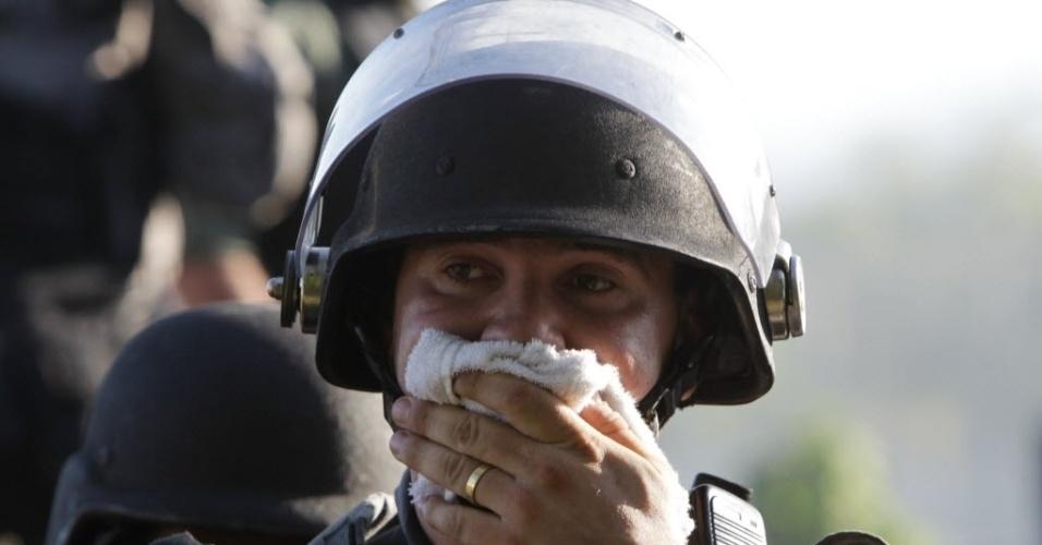 27.06.13 - Policial coloca lenço na boca e no nariz para se proteger do gás lacrimogênio jogado em direção dos manifestantes