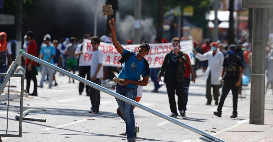 27.jun.2013 - Manifestante atira pedra em direção a policiais durante confronto em protesto que seguia rumo ao Castelão