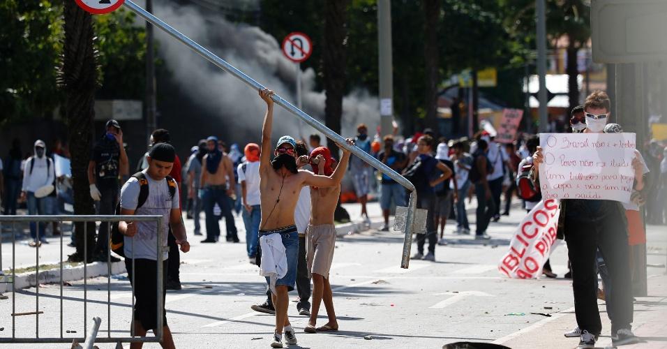27.jun.2013 - Manifestante carrega um poste de sinalização durante confronto com a polícia em protesto que seguia rumo ao Castelão