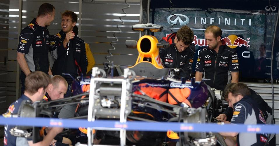 27.jun.2013 - Sebastian Vettel conversa com engenheiro da Red Bull nos boxes de Silverstone