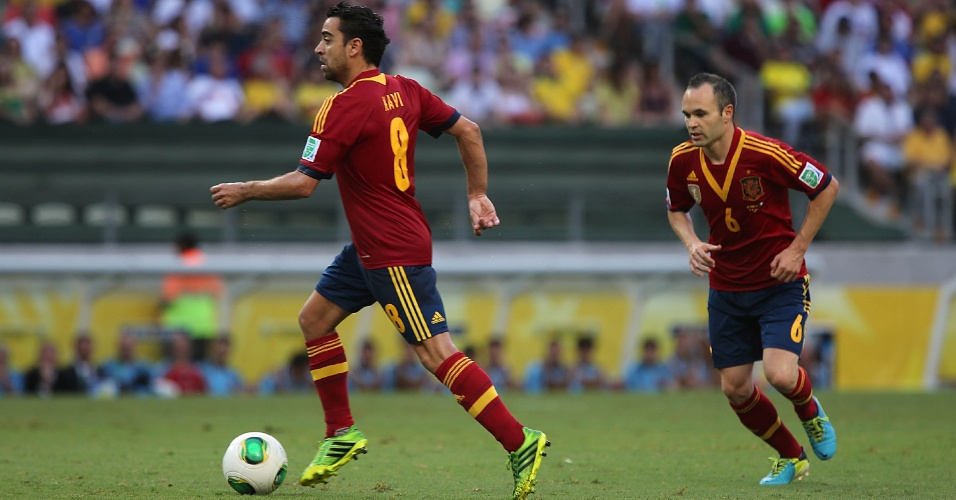 27.jun.2013 - Seguido por Iniesta (d), Xavi parte com a bola dominada em lance da semifinal da Copa das Confederações no Castelão