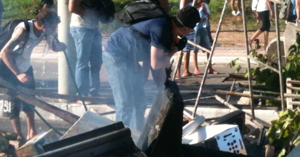27.jun.2013 -Manifestantes fazem barricada para se proteger da polícia