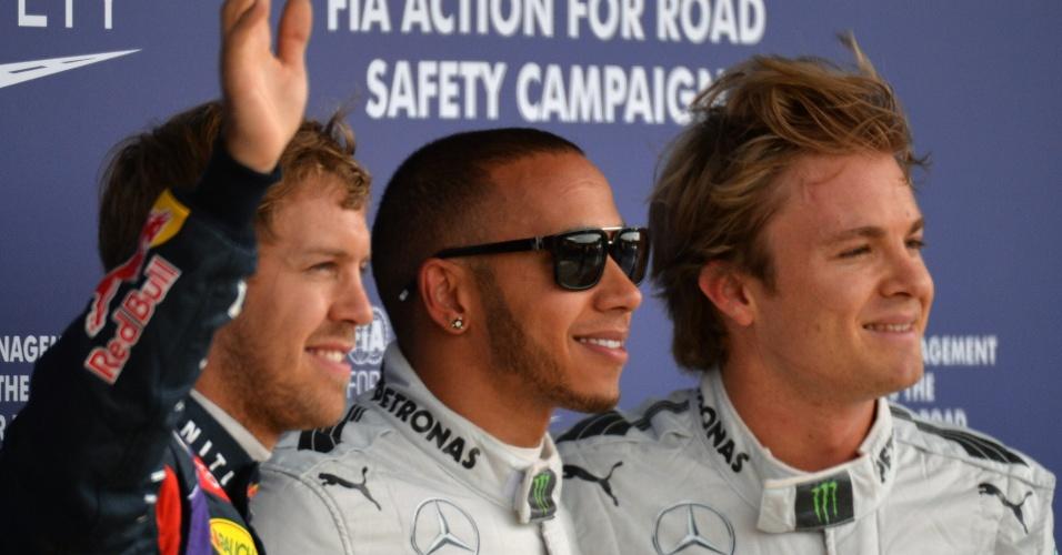 29.jun.2013 - Pole position do GP da Inglaterra, Lewis Hamilton (c) posa com Nico Rosberg (d, que larga em segundo) e Sebastian Vettel (3º)