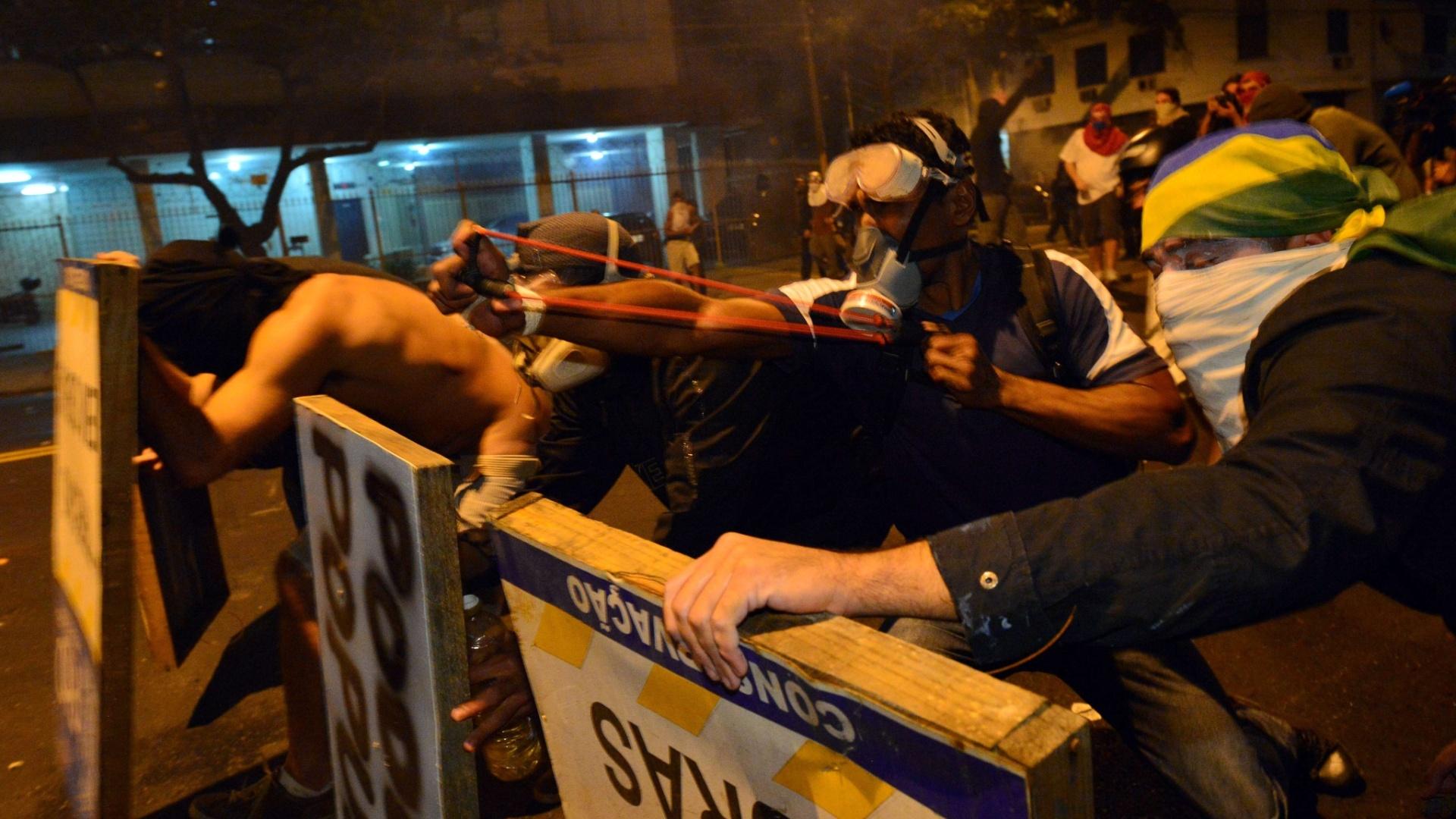 30.jun.2013 - Manifestante se esconde atrás de placas e usa estilingue para atirar contra a polícia durante protesto