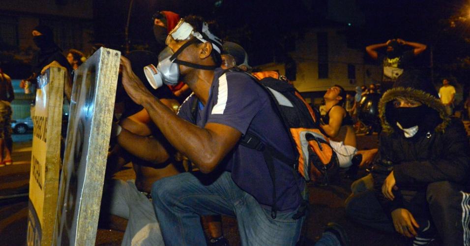 30.jun.2013 - Manifestantes entram em confronto com a polícia perto do Maracanã e usam placar para se proteger