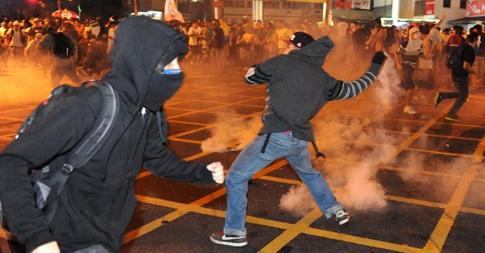 30.jun.2013 - Manifestantes respondem às bombas dos policiais com objetos em protesto no Rio de Janeiro