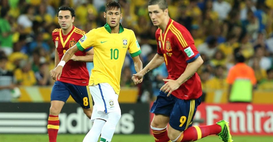 30.jun.2013 - Observado por Torres e Xavi, Neymar toca a bola durante final entre Brasil e Espanha