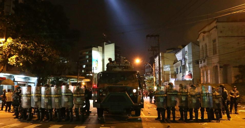 30.jun.2013 - Policiais fazem cordão para conter manifestantes perto do Maracanã
