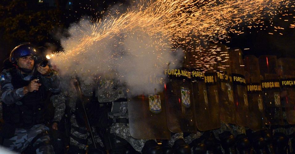 30.jun.2013 - Policial atira em direção aos manifestantes que protestam no Rio de Janeiro