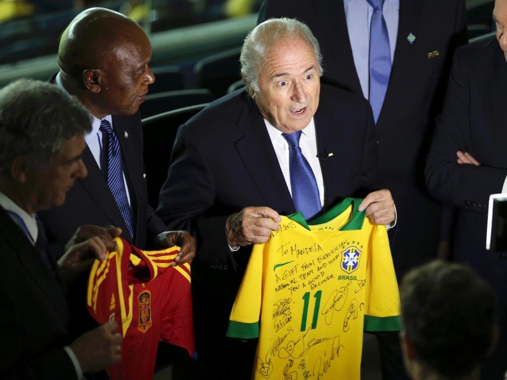 30.jun.2013 - Presidente da Fifa, Sepp Blatter, concede entrevista com uma camisa autografada do Brasil