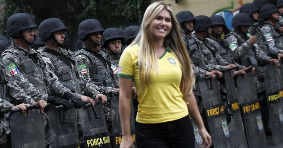 30.jun.2013 - Torcedora do Brasil passa perto de policiais nas cercanias do Maracanã