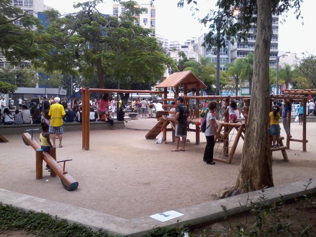 Crianças brincam no parquinho da praça em meio à manifestação