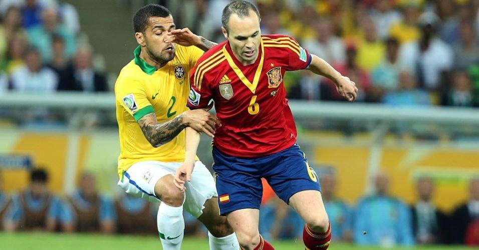 Iniesta (dir.), meia da Espanha, controla a bola com a marcação do brasileiro Daniel Alves