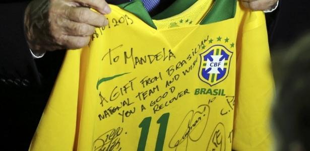 Joseph Blatter, presidente da Fifa, segura camisa do Brasil autografada pelos jogadores e que será levada para Nelson Mandela, ex-presidente da África do Sul que vem sofrendo com problemas de saúde