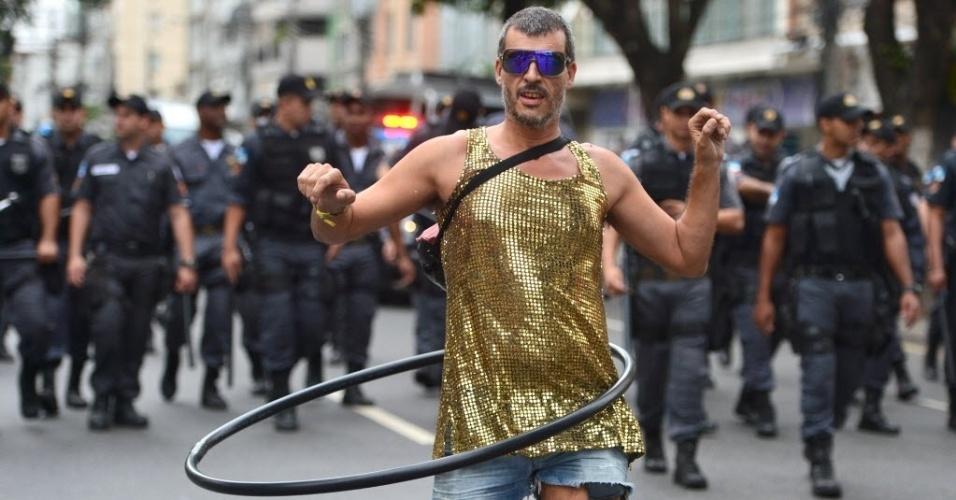 Manifestante inova e rebola no bambolê vigiado por policiais próximos ao Maracanã