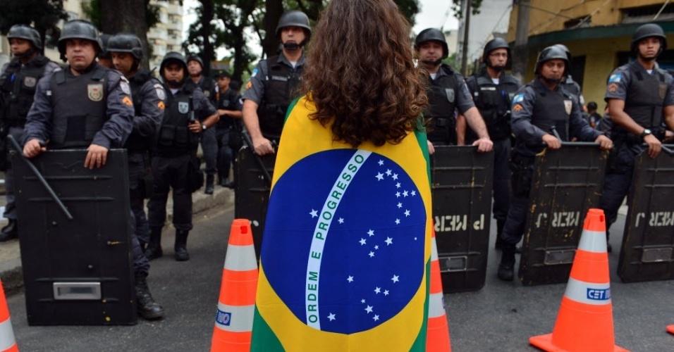 Manifestante se coloca à frente de policiais. Protesto no Rio é pacífico