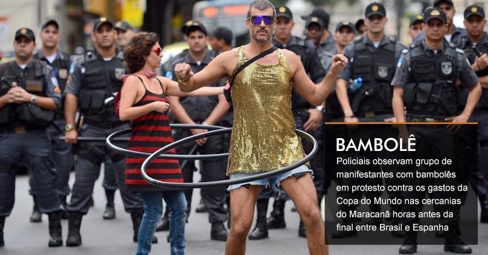 Policiais observam grupo de manifestantes com bambolês em protesto contra os gastos da Copa do Mundo nas cercanias do Maracanã horas antes da final entre Brasil e Espanha