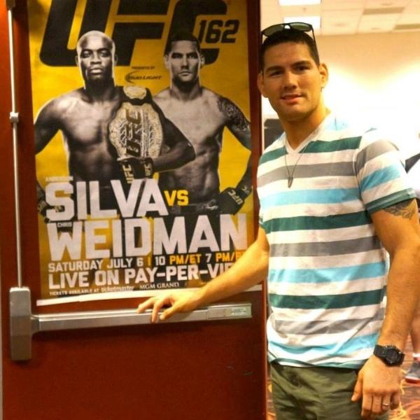 02.jul.2013 - Chris Weidman posa em frente ao pôster do UFC 162, em que luta pelo cinturão contra o lendário Anderson Silva