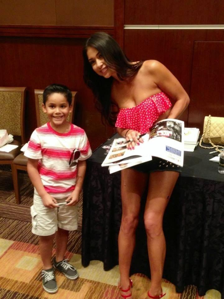 04.jul.2013 - Ring girl Arianny Celeste posa para foto com fã mirim durante evento do UFC em Las Vegas