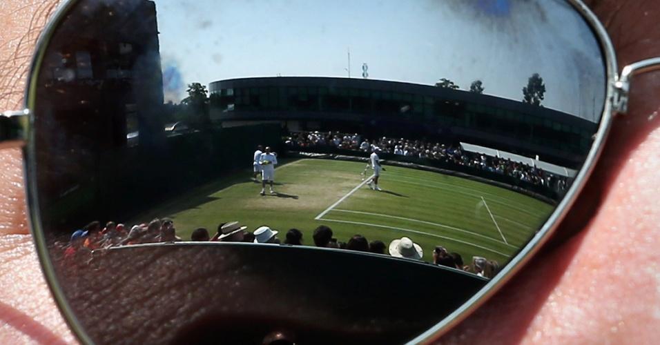 05.jul.2013 - Imagem refletida em óculos mostra Novak Djokovic se aquecendo para enfrentar Juan Martin del Potro pelas semifinais de Wimbledon