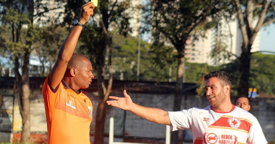 Jogador do Estrela Vermelha reclama ao receber cartão amarelo em partida da Copa Kaiser contra o Capim Maluco
