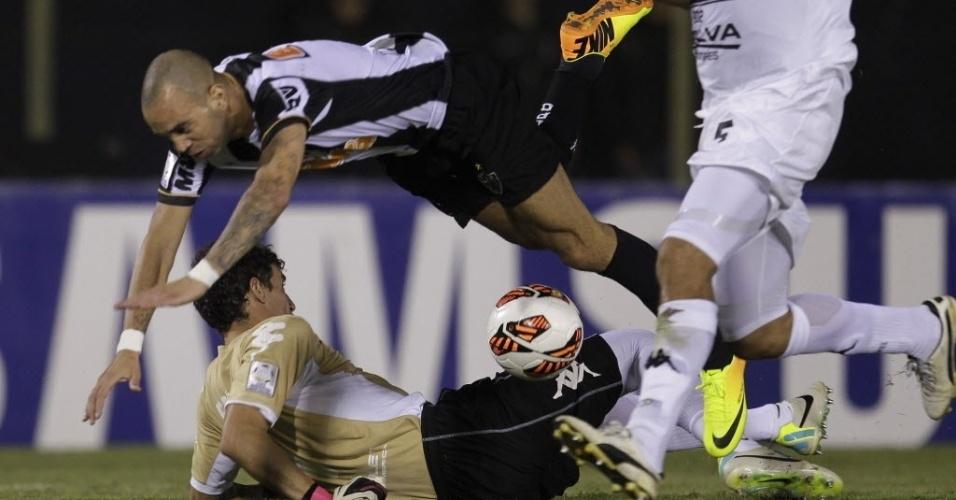 17.07.2013 - Diego Tardelli, atacante do Atlético-MG, divide a bola com o goleiro Martin Silva, do Olímpia, durante partida em Assunção