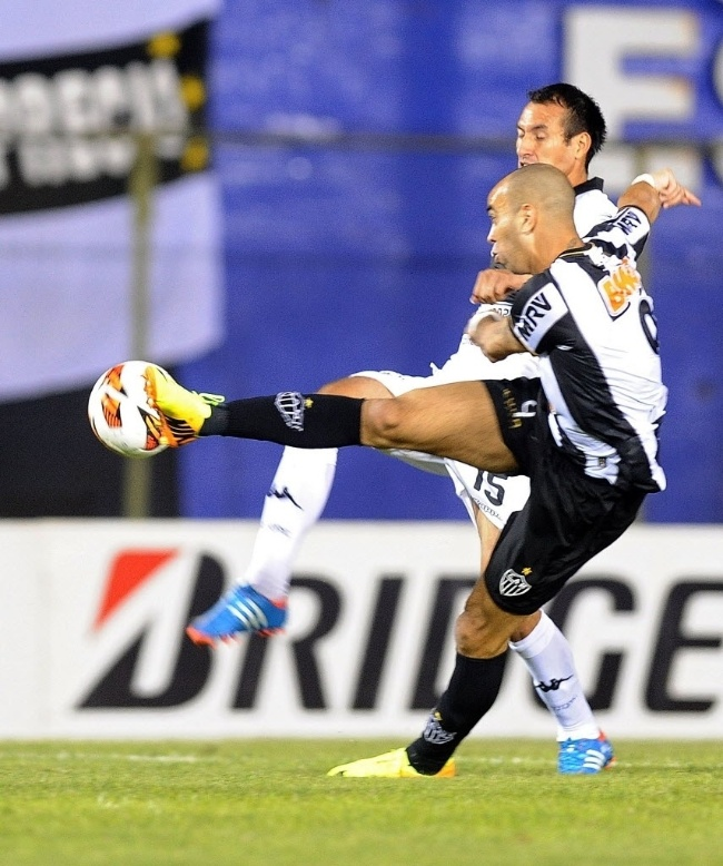 17.07.2013 - Diego Tardelli é travado por Herminio Miranda, do Olímpia, em tentativa de chute a gol na decisão da Libertadores