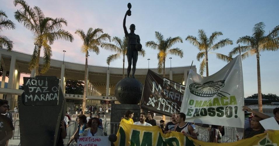 21.07.13 - Manifestantes protestam próximo da estátua de Bellini levantando a taça de campeão da Copa de 58 e 62