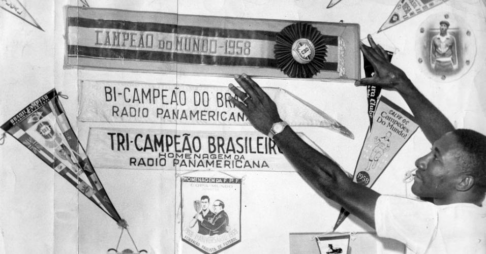 Dez.1960 - Djalma Santos, então jogador do Palmeiras, exibe flâmulas dos títulos conquistados