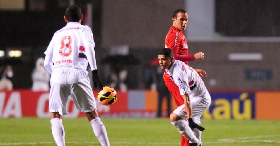 24.jul.2013 - Paulo Henrique Ganso domina a bola após disputa do volante Denilson com jogador do Internacional, no Morumbi