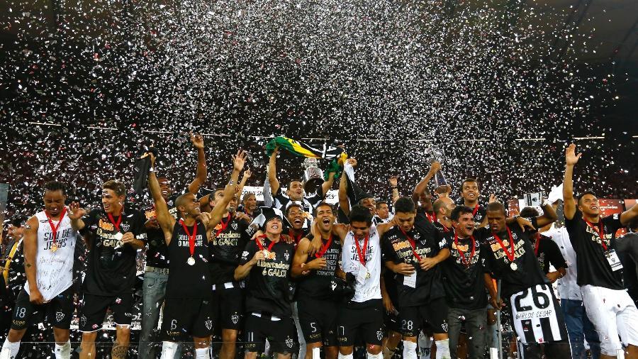 Jogadores do Atlético-MG erguem a taça e celebram a conquista da Libertadores 2013 - Marcus Desimoni/UOL