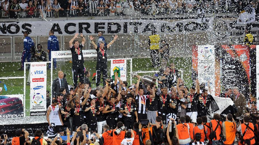 Zagueiro e capitão Réver foi o responsável por erguer a taça do título do Galo na Libertadores de 2013 - AFP PHOTO / EVARISTO SA
