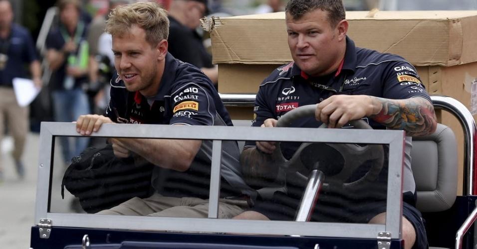 Sebastian Vettel pega uma carona com integrante da Red Bull no paddock de Budapeste