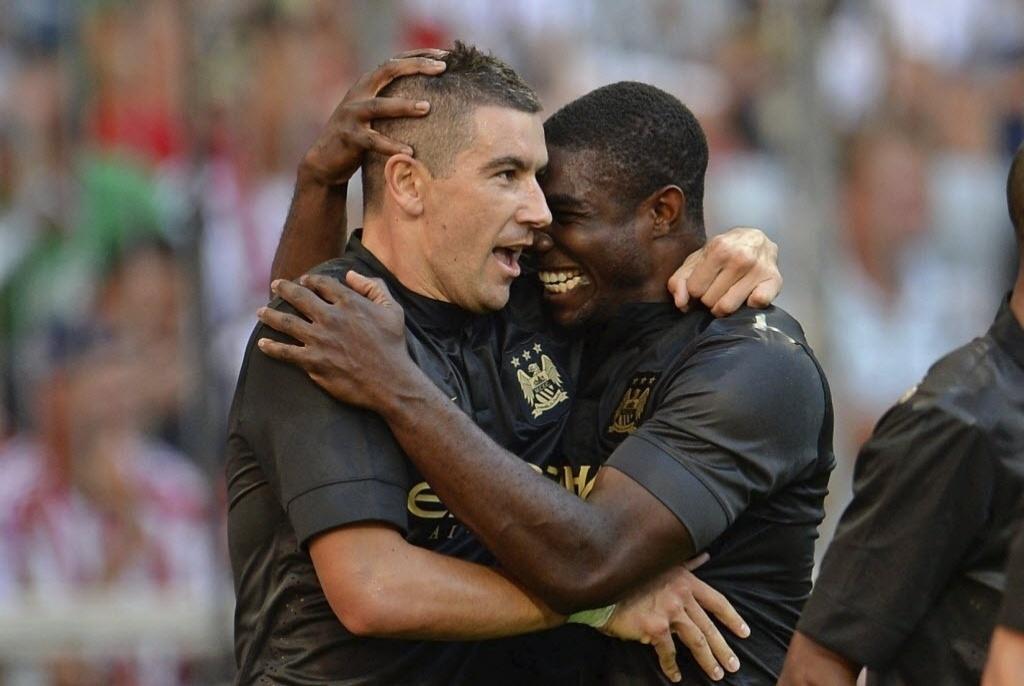 31.jul.2013 - Aleksandar Kolarov (e) celebra com seu compaheiro Micah Richards o terceiro gol do Manchester City no jogo contra o Milan