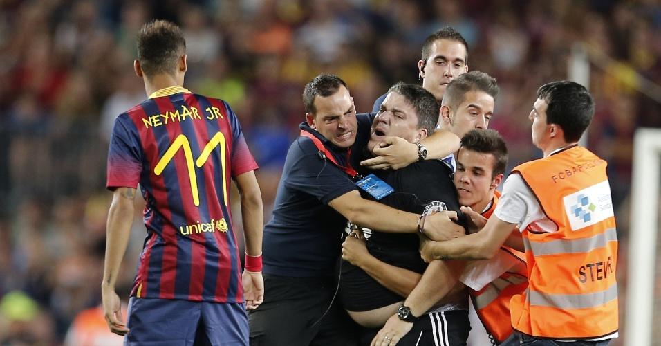 01.ago.2013 - Torcedor invade o campo e é contido por seguranças ao tentar se aproximar de Neymar no jogo entre Barcelona e Santos