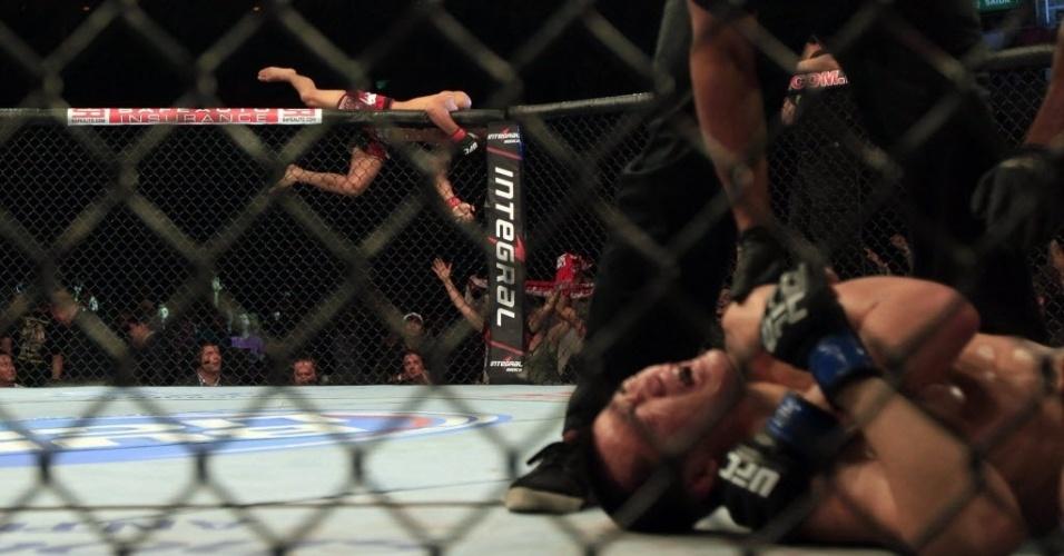 04.ago.2013 - José Aldo salta a grade, enquanto o Zumbi Coreano grita de dor por uma lesão no ombro no fim do combate no Rio