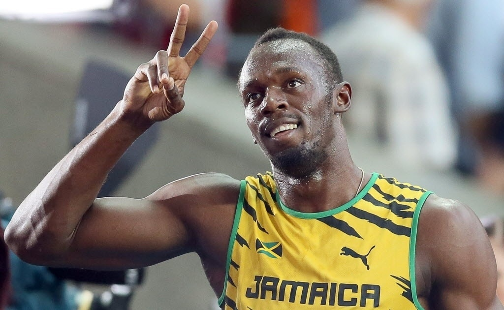 10.08.2013 - Usain Bolt acena para a torcida depois de vencer com tranquilidade sua bateria nas eliminatórias dos 100 m do Mundial de Moscou