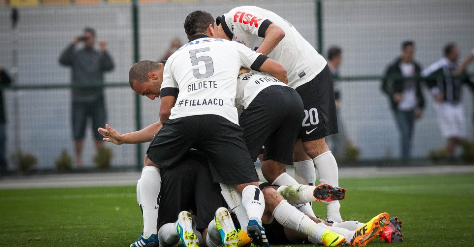 11.08.2013 - Pato ajoelha e é abraçado pelos companheiros após marcar o segundo do Corinthians contra o Vitória