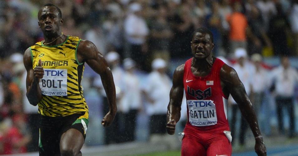 11.ago.2013 - Jamaicano Usain Bolt cruza a linha de chegada dos 100m seguido do norte-americano Justin Gatlin