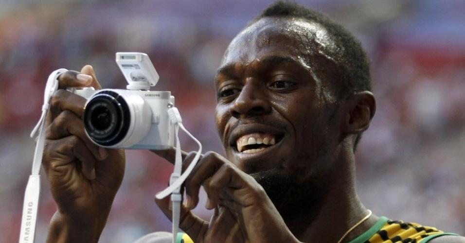 17.ago.2013 - Bolt brinca com câmera após levar o ouro nos 200 m