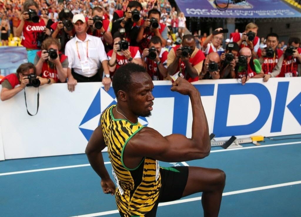 17.ago.2013 - Usain Bolt mostra seus músculos após conquistar o ouro nos 200 m em Moscou