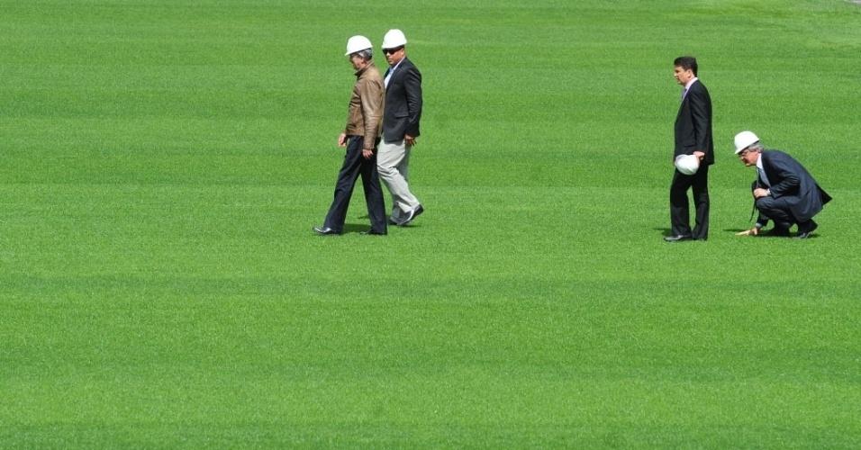 19.ago.2013 - Comitiva do COL e o secretário-geral da Fifa, Jérôme Valcke (d), inspecionam o gramado do Itaquerão