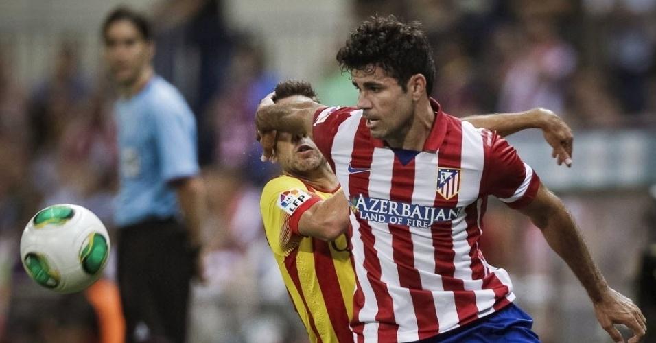 21.ago.2013 - Atacante brasileiro Diego Costa, do Atlético de Madri, protege a bola e tenta evitar a marcação de Jordi Alba, do Barcelona, durante Supercopa da Espanha