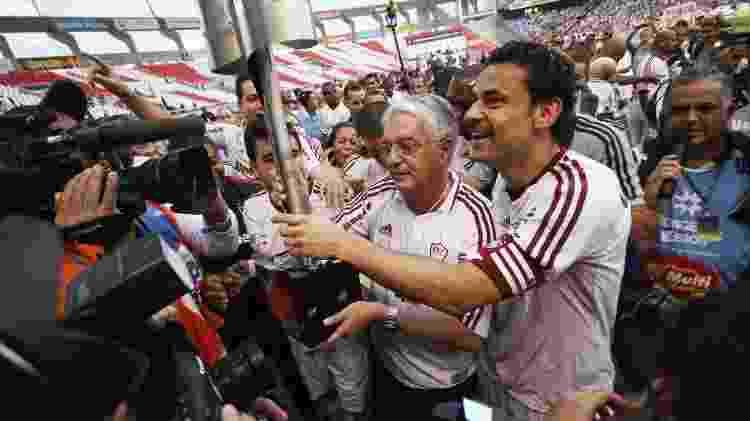 23.ago.2013 - Presidente da Unimed-RJ, Celso Barros (centro) ergue o troféu do Brasileirão de 2012 com Fred - Ricardo Ayres/Photocamera - Ricardo Ayres/Photocamera