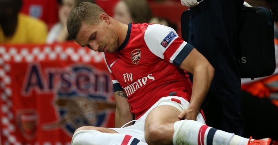 27.ago.2013 - Lukas Podolski senta no gramado após sentir lesão na região da coxa esquerda na partida do Arsenal contra o Fernerbahce, pela Liga dos Campeões