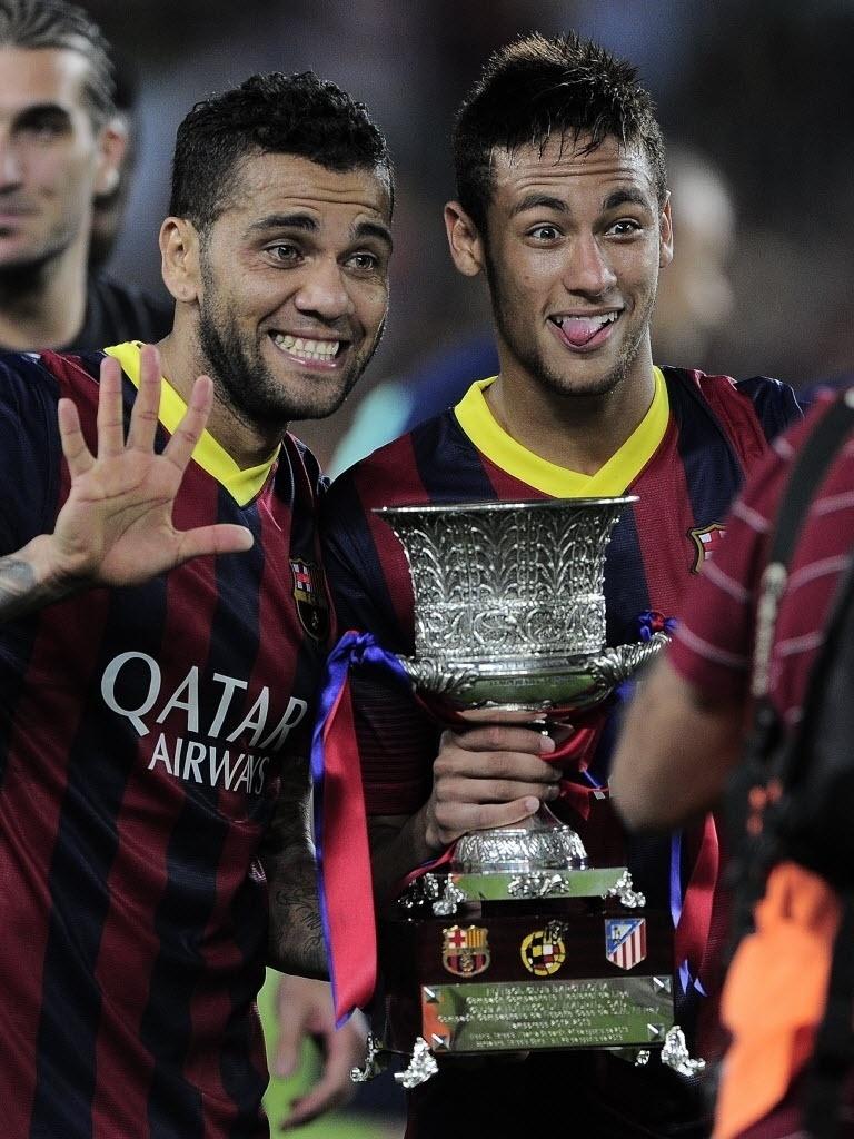 28.ago.2013 - Daniel Alves e Neymar fazem careta ao exibir o troféu de campeão da Supercopa da Espanha conquistado pelo Barcelona