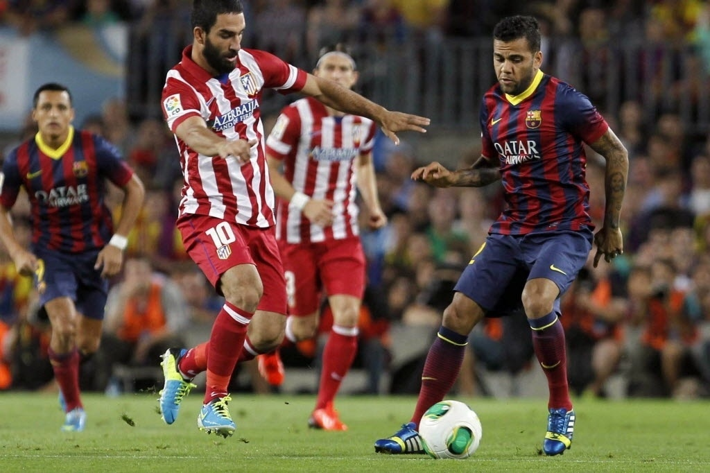 Dani Alves (dir.), lateral brasileiro do Barcelona, controla a bola na partida contra o Atlético de Madri pela Supercopa da Espanha
