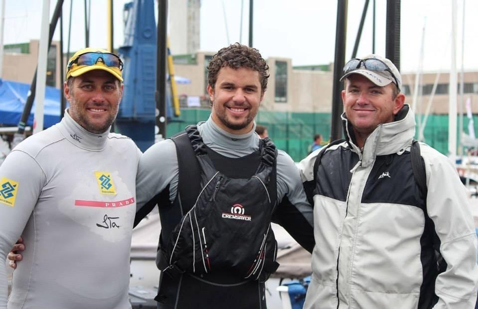 Campeão mundial, Jorginha ZArif comemora ao lado de Bruno Prada (esq.), brasileiro que também compete na Finn, e Rafael Trujillo, seu técnico