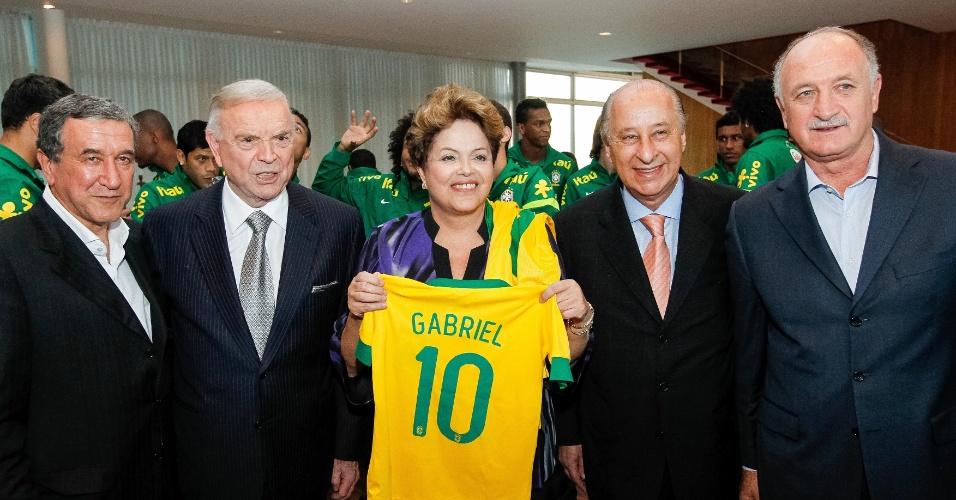2/9/2013 - Presidente Dilma Rousseff posa com a camisa da seleção brasileira ao lado do presidente da CBF, José Maria Marin, do técnico da seleção, Luiz Felipe Scolari, e o coordenador técnico Carlos Alberto Parreira, e do presidente da FPF e vice da CBF, Marco Polo del Nero