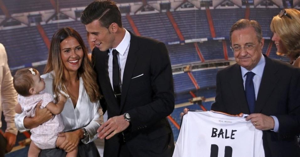 Bale e a namorada Rhys Jones cuidam do bebê Alba Violet Jones (filha do atleta) enquanto o presidente do Real Madrid, Florentino Perez, segura uniforme do atleta